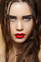 Hot model with sexy lips makeup, strong eyebrows, wet hairstyle