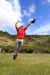 Baseball player jumps high to catch a ball