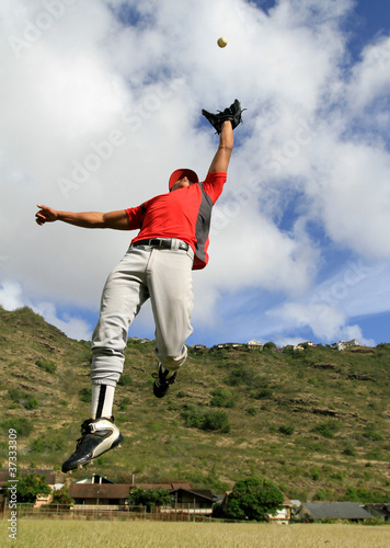 Baseball player jumps high to catch a fly ball
