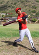 Baseball batter mid-swing in an open grassy field