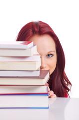 Mädchen schaut hinter Bücherstapel vor