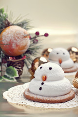 Two marshmallow snowmen biscuits with Christmas decorations