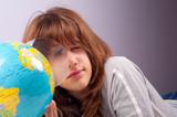 Pretty teenage girl studies earts geography on little globe poster