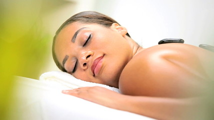 Ethnic Girl Relaxing with Hot Stone Spa Therapy