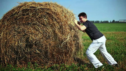 Young man fighting with haystack