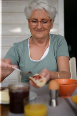 Elderly woman eating balanced breakfast