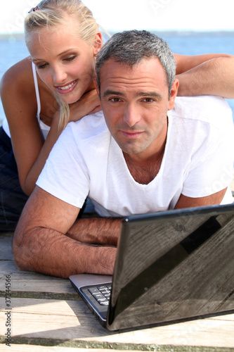 Couple with laptop on jetty
