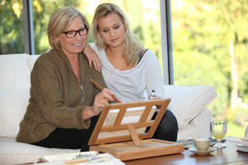 Woman showing her granddaughter how to paint