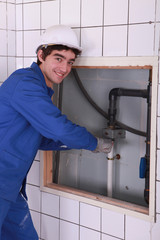 Young plumber working in bathroom