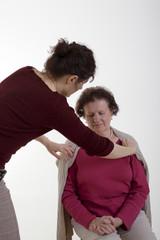 Junge Frau hilft Seniorin beim Anziehen