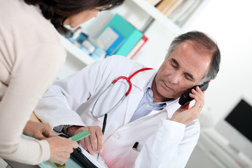 Doctor talking on the phone during a consultation