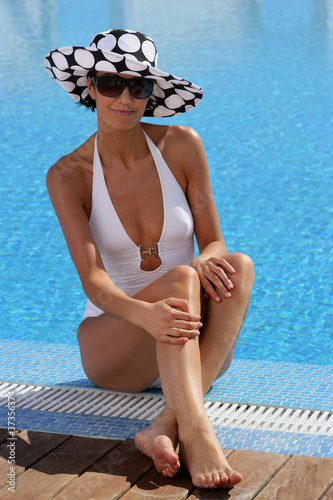 Gorgeous woman sitting at a poolside