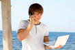 Young man with mobile phone using laptop at beach