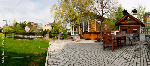 Rear view of luxury home backyard with swimming pool, patio and - 37363934