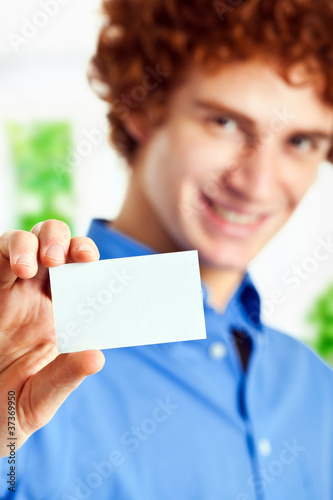 Handsome happy guy showing the blank card