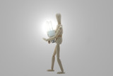 Wooden Manikin Doll Holding Low Energy Bulb poster