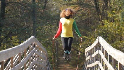 girl with skipping rope on a bridge