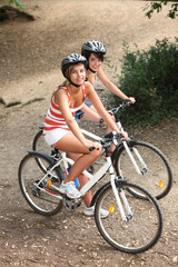 Young girls riding bikes in the woods