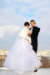 happy groom and bride with bouquet of roses embrace and look