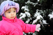 Little beautiful girl dressed pink jacket stands near green tree