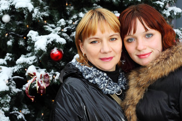 Two women stands near green tree with snow; Mother and daughter