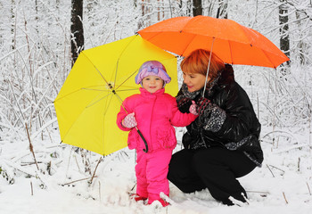 Grandmother and granddaughter with yellow and orange umbrella