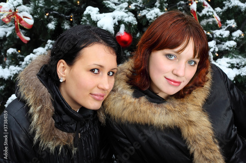 Two young women stands near green tree with snow