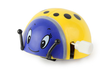 bright toy clockwork yellow ladybird with blue face on white