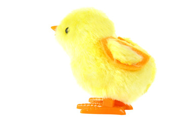 side view of clockwork toy fluffy yellow chick with orange feet