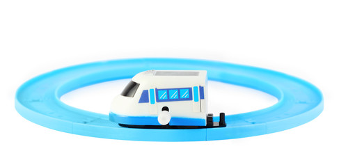 bright clockwork toy white train with blue windows on railroad