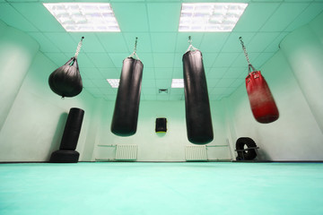 empty light green room, where black and red punching bag hang