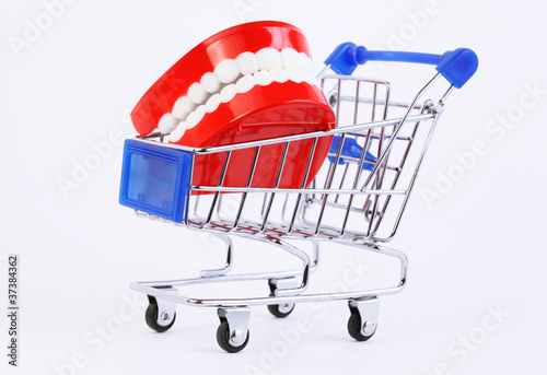 small toy jaw with white teeth in purchasing cart on white