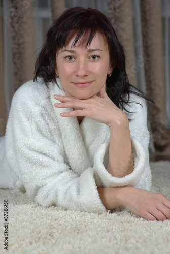 Smiling female lying on a carpet
