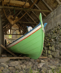 Traditional Faroese fishing boat made of wood in an old bo