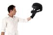 Homme debout de profil tenant son casque de moto