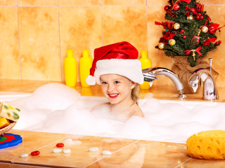 Kid washing in bath. Christmas.