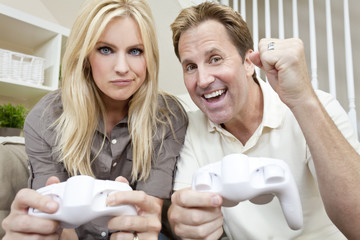 Married Couple Having Fun Playing Video Console Game