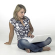 relaxed young girl sitting on the ground while computing