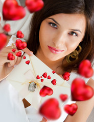 Young pretty attractive smiling woman with heart lying relaxed a