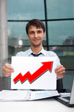 Attractive man in business suit with sign of up graph sitting at