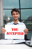 Attractive man in business suit with acceptance sign sitting at