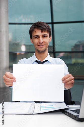 Attractive man in business suit with blank sign sitting at his o
