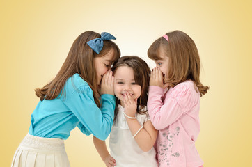 cute young sisters sharing a surprising secret, isolated on whit