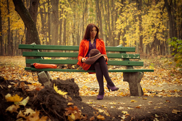 girl sitting on a park bench in late autumn