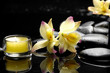 Reflection of burning candle and zen stones with yellow orchid