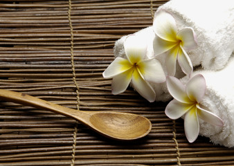 Roller Spa towels with frangipani flower and spoon on mat