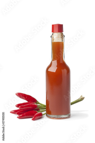 Bottle with hot chili pepper sauce and fresh tabasco peppers