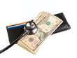 Stethoscope on wallet with stack of ten dollar bills