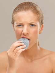 portrait woman biting a metal dish scrubber