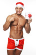 Image of sexy male wearing xmas costume and holding a gift